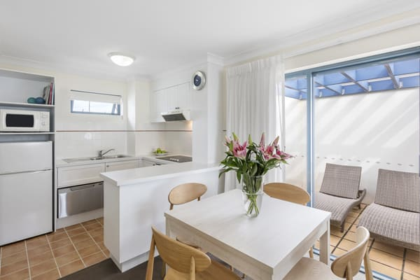 air conditioned open plan kitchen with dining table and modern appliances including full size fridge, microwave and kettle for hotel guests to use