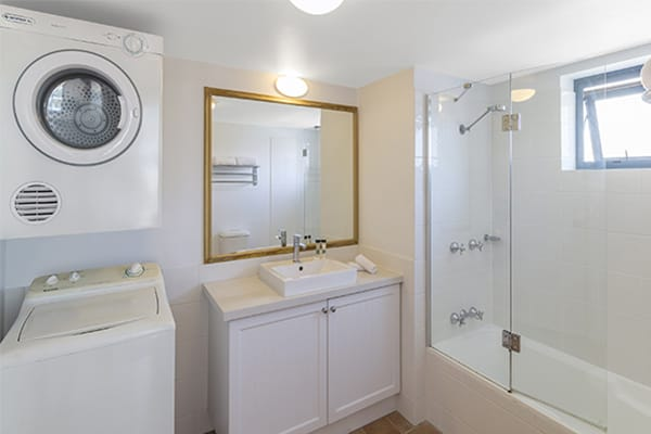 washing machine and clothes dryer in the bathroom at one bedroom ocean premier apartment at Oaks Calypso Plaza resort in Gold Coast, Australia