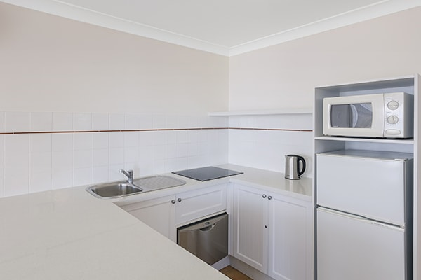 kitchen with fridge, microwave, kettle, oven and stove top at one bedroom ocean premier apartment at Oaks Calypso Plaza resort in Gold Coast, Australia