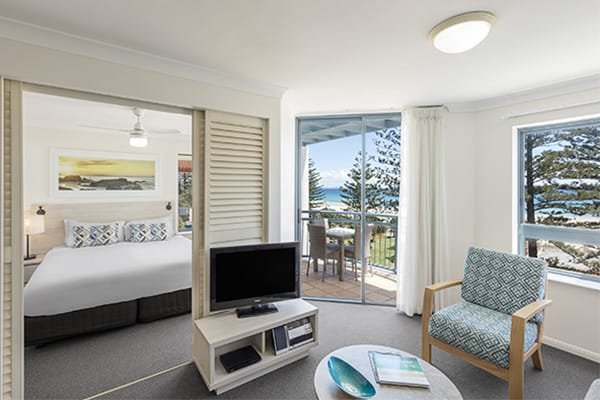 Spacious living room with TV, sofa, round tale and ocean view at one bedroom ocean premier apartment at Oaks Calypso Plaza resort in Gold Coast, Australia