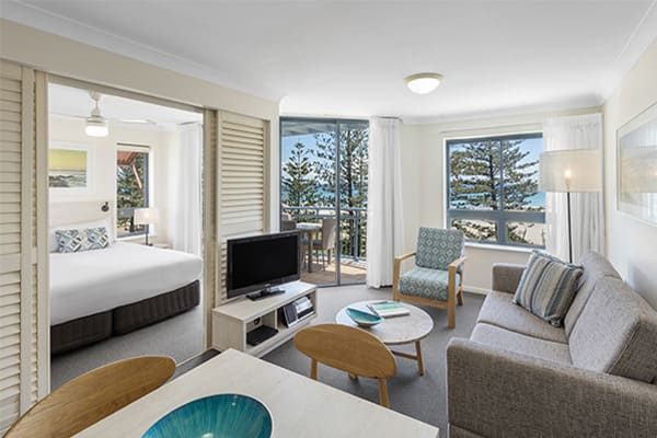 Spacious living room with TV, sofa, round tale and ocean view connecting to bedroom at one bedroom ocean premier apartment at Oaks Calypso Plaza resort in Gold Coast, Australia