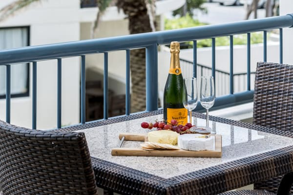 table with bottle of champagne, cheese and biscuits on balcony of 1 bedroom apartment at Oaks Calypso Plaza hotel resort