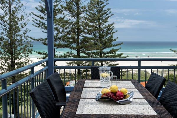 balcony of two bedroom apartment with table and chairs and views of beach and ocean in Coolangatta, Gold Coast, Australia