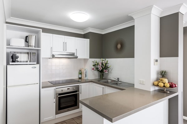 kitchen with modern appliances including large fridge, oven and microwave in 2 bedroom hotel apartment in Coolangatta