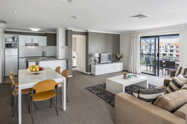 large living room with dining table, comfortable chairs and air conditioning in Gold Coast hotel