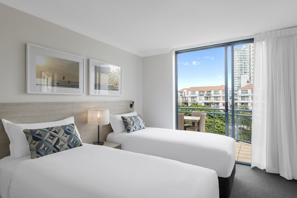 2 single beds in two bedroom apartment close to beach with balcony views of ocean at Oaks Calypso Plaza hotel resort on Gold Coast, Australia