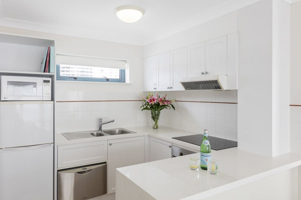 modern kitchen with large preparation bench, microwave, fridge and oven at Oaks Calypso Plaza resort in Coolangatta, Gold Coast
