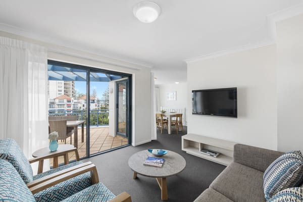 air conditioned living room with comfortable couches and Foxtel on TV with balcony furniture and views of beach and ocean in Coolangatta