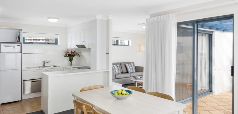 air conditioned open plan living room in two bedroom apartment with courtyard and comfortable furniture
