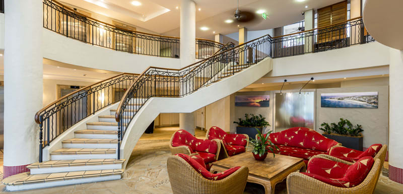 reception area at Oaks Calypso Plaza resort with spiral staircase, nice furniture and air conditioning in Coolangatta