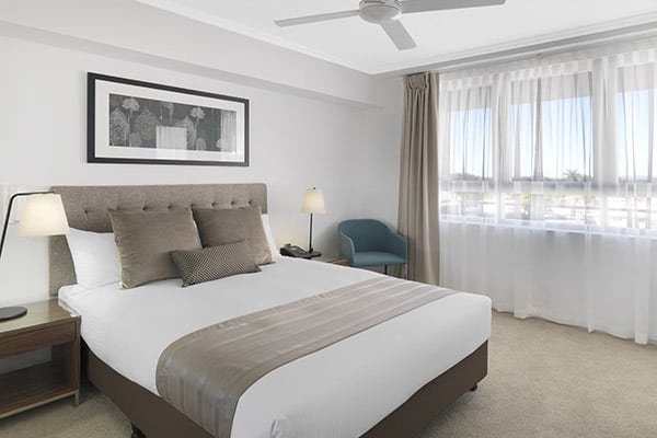 large comfortable queen size bed in 1 bedroom apartment with air conditioning in Mackay, Queensland
