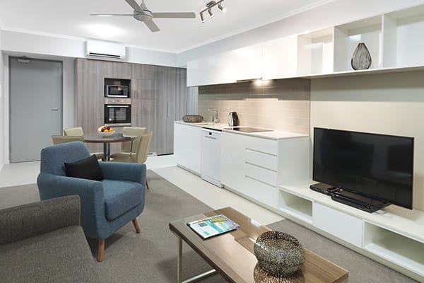 1 bedroom hotel apartment large living room with TV, air conditioner and kitchen with microwave at Oaks Carlyle