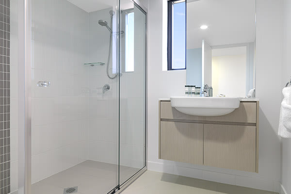 en suite bathroom of two bedroom apartment at Oaks Carlyle hotel in Mackay with large adjustable, shower, toilet and clean towels on rack