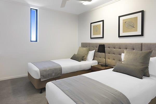 2 single beds with sidelamp in two bedroom apartment at Oaks Carlyle hotel in Mackay, Queensland, Australia
