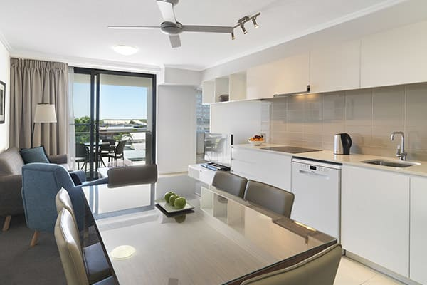 kitchen with dining room table, kettle and dishwasher in two bedroom apartment at Oaks Carlyle hotel in Mackay, QLD