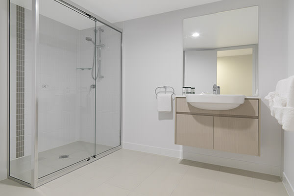 en suite bathroom with large shower and clean towels in two bedroom hotel apartment on Alfred Street in Mackay