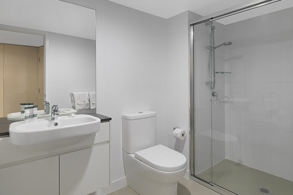 en suite bathroom with toilet, shower, toilet and cabinet with mirror in 2 bedroom dual key apartment
