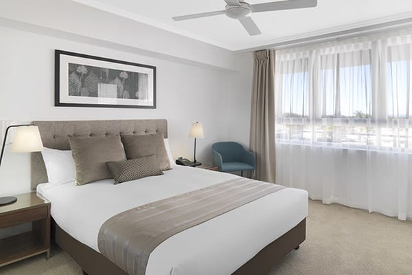 two bedroom apartment with queen size bed and ceiling fan at Oaks Carlyle hotel near Harbour Beach in Mackay