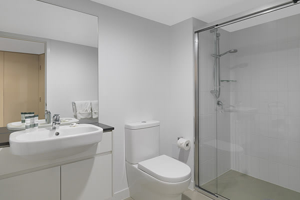 en suite bathroom with toilet, shower, mirror and large mirror in Oaks Carlyle hotel room in Mackay