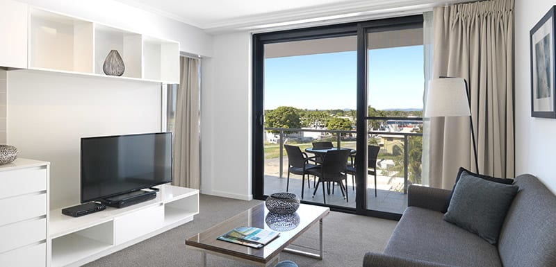 air conditioned living room with TV and glass doors leading out to balcony with views of Mackay city in Queensland, Australia