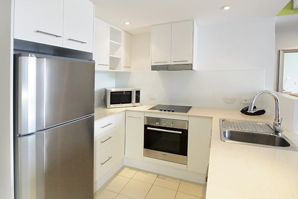 one bedroom apartment kitchen with microwave, oven and full-size fridge at Gateway on Palmer hotel in South Townsville