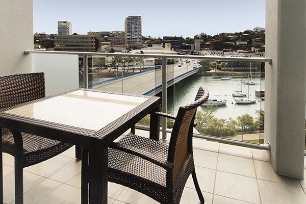 1 bedroom apartment balcony with chairs and table and views of Ross Creek in Townsville