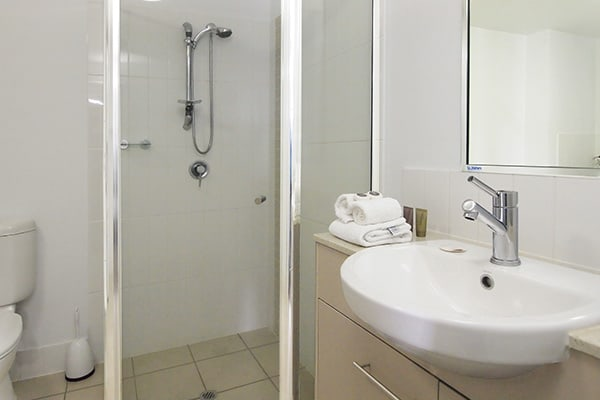 en suite bathroom with shower, toilet, clean towels and big mirror at Oaks Gateway Suites hotel in South Townsville