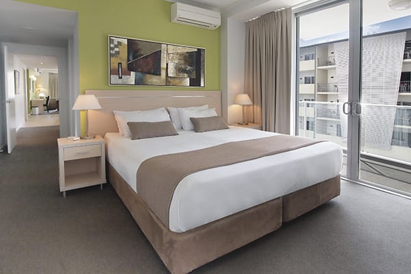 queen size bed in 2 bedroom air conditioned apartment at Oaks Gateway Suites hotel in Townsville