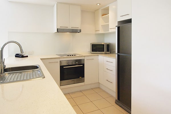 modern kitchen with full-size refrigerator, microwave and oven in 2 bedroom hotel apartment near Museum of Tropical Queensland, Townsville