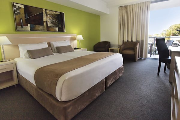 Hotels in Townsville with king size bed in hotel room bedroom with desk for work and balcony with views of Townsville at Oaks Gateway Suites