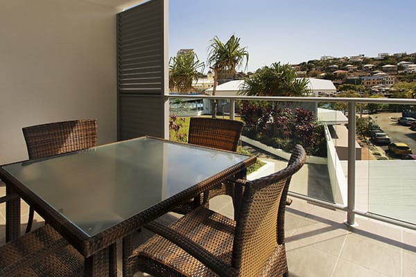 hotel room balcony with table and chairs and view of Townsville harbour at Oaks Gateway Suites hotel accommodation