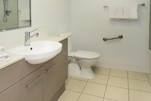 en suite bathroom with shower, toilet and big mirror at Gateway on Palmer hotel on Dibbs St in South Townsville
