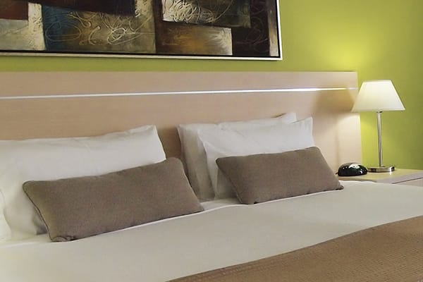 clean pillows on queen size bed in affordable Townsville holiday apartments hotel room bedroom at Oaks Gateway Suites in South Townsville