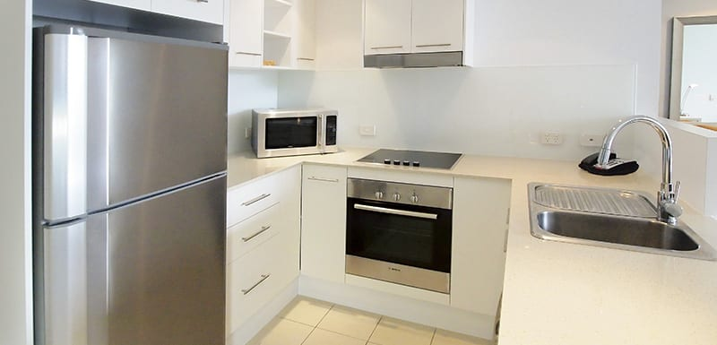 1 bedroom apartment kitchen with big refrigerator, microwave, oven and cooking stove top at Gateway on Palmer in South Townsville