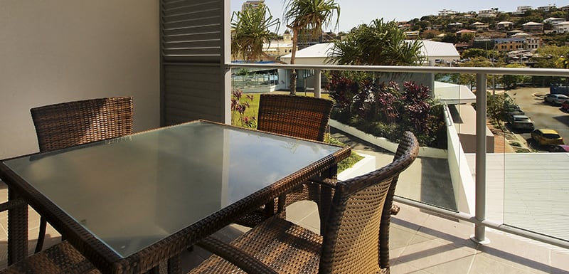 table and chairs on balcony at 2 bedroom hotel accommodation apartment with views of Townsville and harbour at sunset