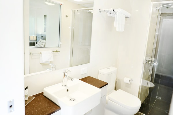 en suite bathroom with shower, toilet and clean towels in one bedroom apartment at Oaks Grand Gladstone hotel