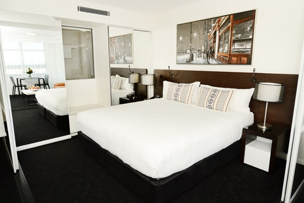 queen size bed in 1 bedroom apartment with air con and large wardrobe for storage at Oaks Grand Gladstone hotel