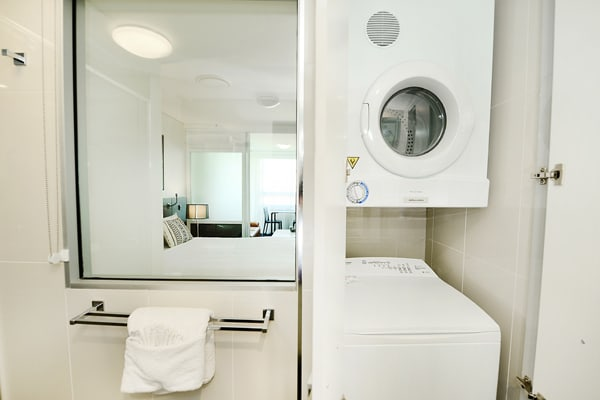 washing machine and dryer in bathroom of 1 bedroom apartment in Gladstone, Queensland, Australia