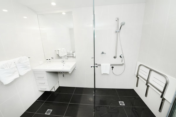 en suite bathroom with disabled access shower in studio hotel room at Oaks Grand Gladstone, Queensland, Australia