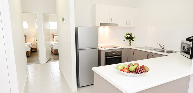 open plan kitchen and living room area with large counter tops, big refrigerator and microwave near Middlemount Airport