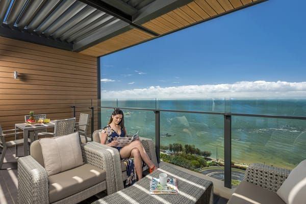 woman sitting on chair on private balcony of 1 bedroom apartment with views of ocean in Redcliffe, Queensland