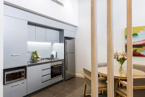 kitchen in 1 bedroom apartment with microwave, full-size fridge and oven at Mon Komo Hotel in Redcliffe, Queensland, Australia