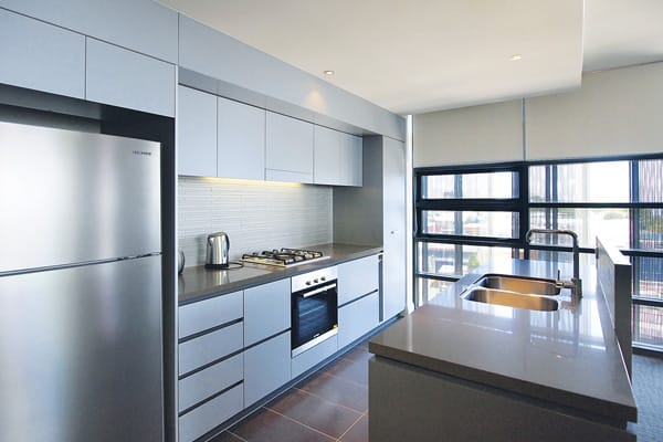 spacious kitchen with large fridge, oven and microwave in 2 bedroom ocean view apartment near beach in Redcliffe