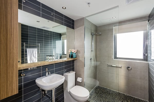 2 bedroom apartments en suite bathroom with big disabled access shower, toilet and mirror at Mon Komo Hotel in Redcliffe