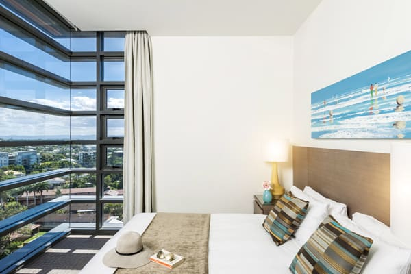air conditioned bedroom with queen size bed in 2 bedroom apartment at Mon Komo Hotel in Redcliffe