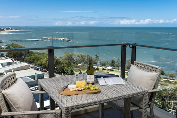 table with wine bottle, cheese and biscuits on balcony of 3 bedroom apartment with views of ocean at Oaks Mon Komo Hotel in Redcliffe