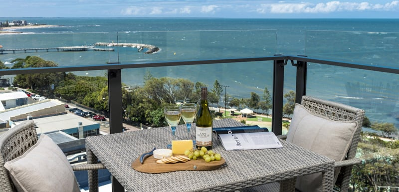 hotel balcony with table and chairs and view of ocean and Sutton Beach in Redcliffe
