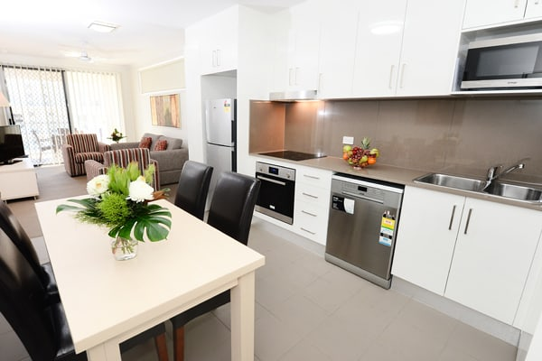 living room with dining table and air conditioner in 2 bedroom apartment at Oaks Moranbah hotel