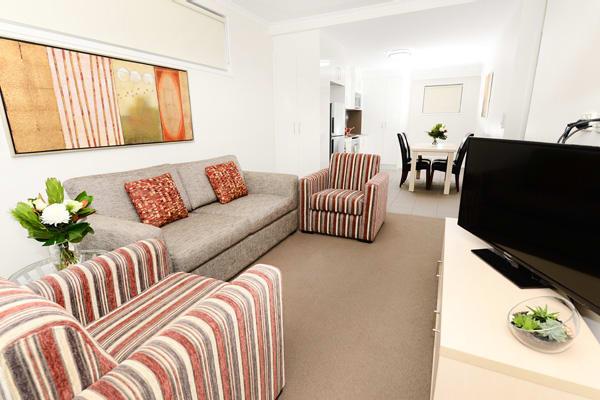 living room in best Moranbah hotels with TV and Foxtel in 2 bedroom apartment at Oaks Moranbah hotel in Queensland, Australia