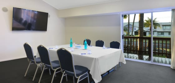 chairs and table in air conditioned room with TV and private balcony for hire for conferences in Caloundra, Sunshine Coast